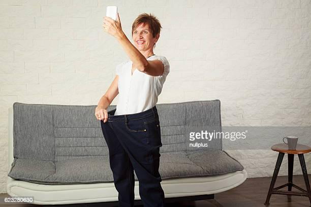 Donna anziana scattare selfie, mostrando la perdita di peso