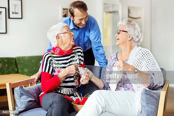 Senior woman talking to man while knitting at nursing home