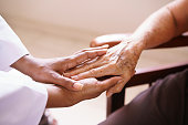 Old people in geriatric hospice: Aged patient receives the visit of a female black doctor. They shake their hands and talk in the hospital.