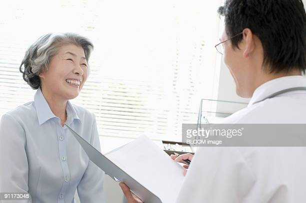 Senior woman talking with doctor, smiling