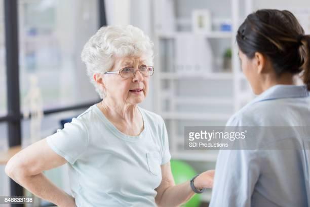 Ältere Frau Gespräche mit Arzt über Rückenschmerzen