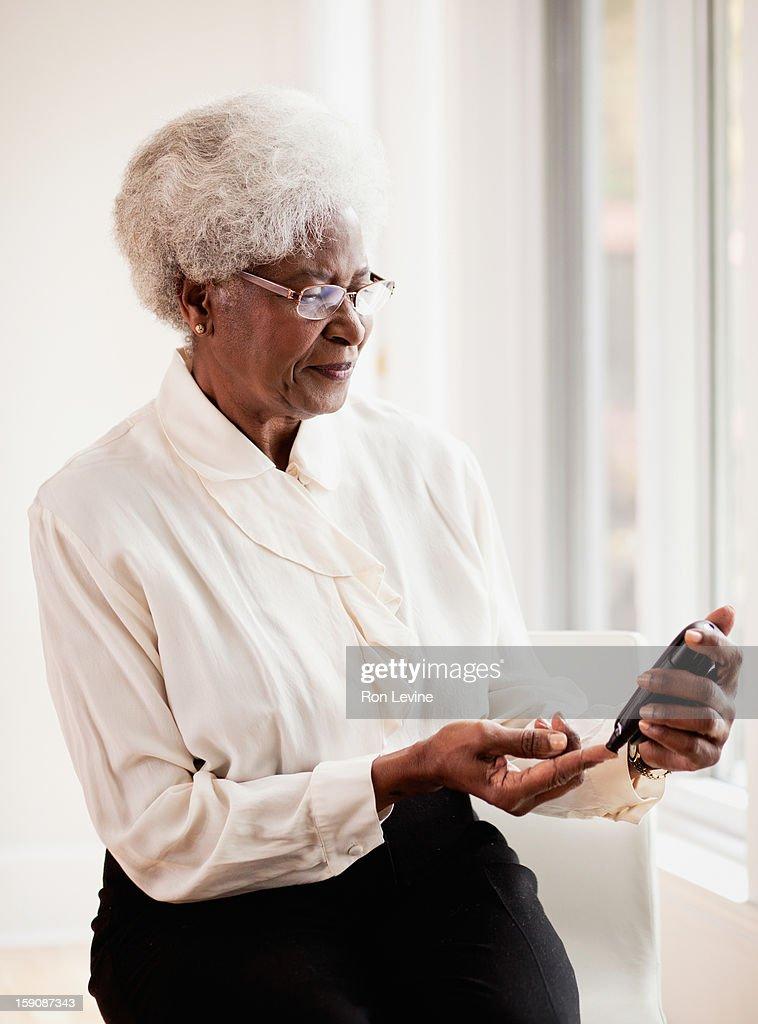 Senior woman testing her blood glucose level : Stock Photo