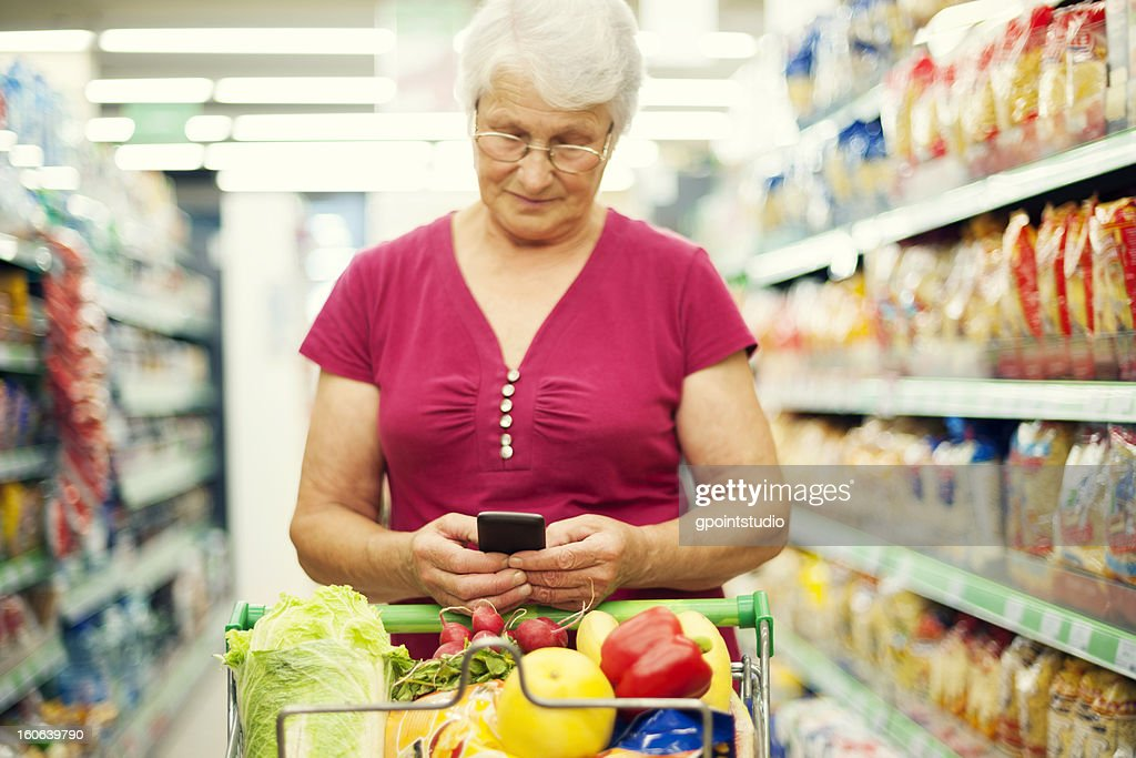 Senior woman texting on mobile phone at supermarket : Stock Photo