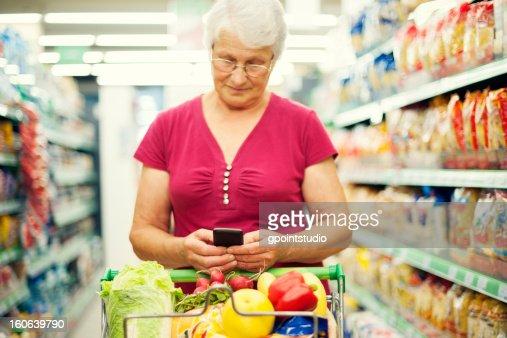 Senior woman texting on mobile phone at supermarket : Stock Photo
