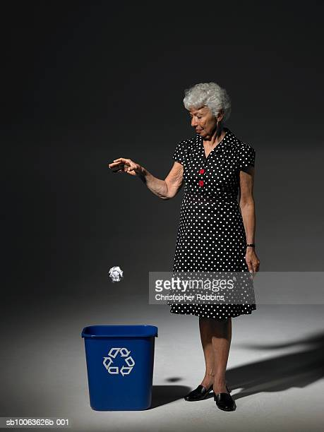Senior woman throwing paper ball to recycling bin