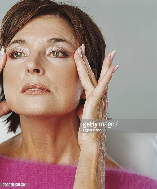 Senior woman touching temples with fingers, close-up