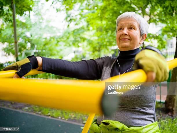 Senior woman trains on exercise machine in public park