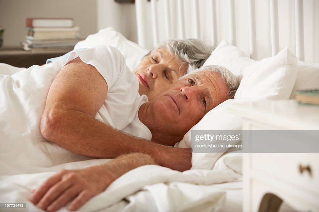 Senior Woman Tries To Be Affectionate Towards Husband In Bed : Stock Photo