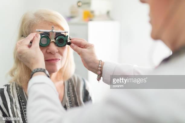 Senior woman trying test frames on