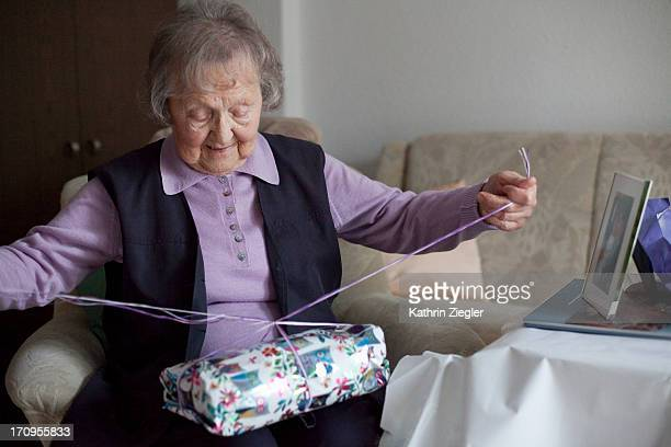 senior woman unwrapping birthday presents