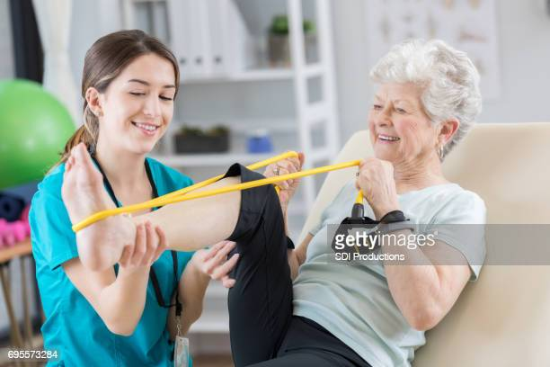 Senior woman uses resistance band during therapy
