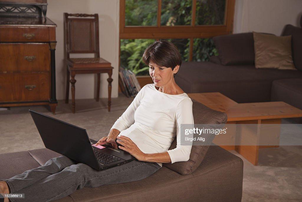 Senior woman using a laptop : Stock Photo