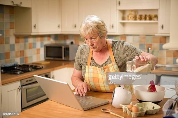 Femme âgée à l'aide d'une recette en ligne