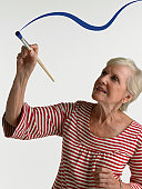 Senior woman using brush with blue paint
