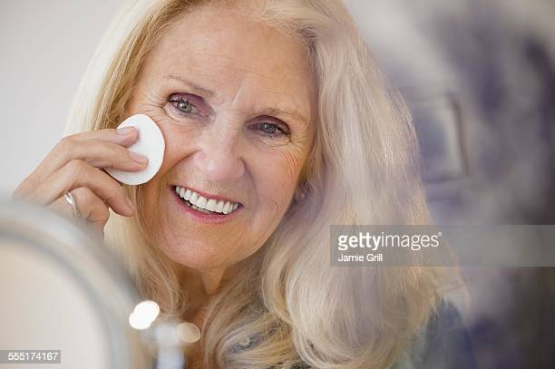 Senior woman using cotton wool pad