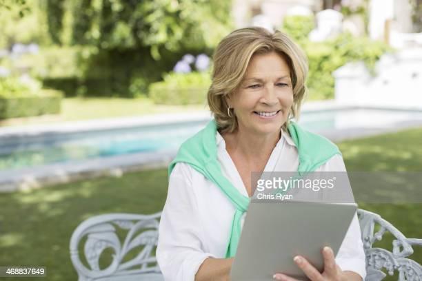 Senior woman using digital tablet in backyard