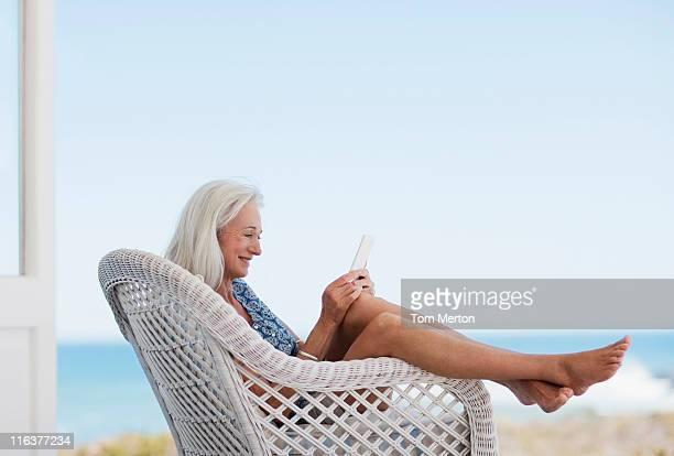 Senior woman using digital tablet in chair