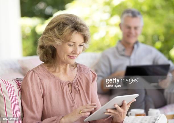 Senior woman using digital tablet on patio