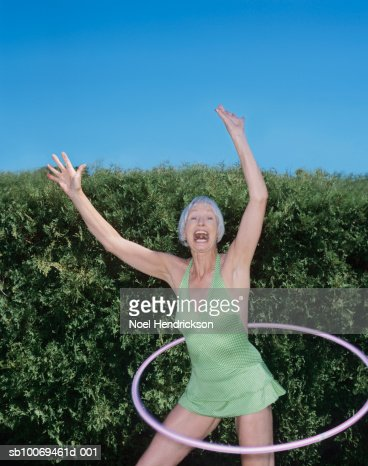 Senior woman using hula hoop by hedge, portrait : Stock Photo