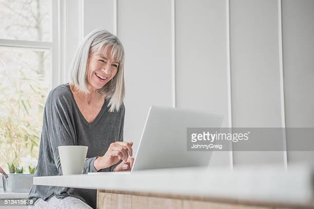 Senior mujer usar computadora portátil en su hogar, Riendo