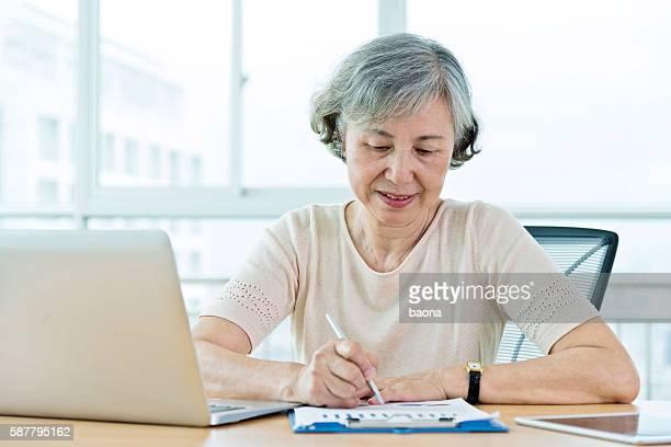 ノートパソコンを使う老人女性自宅で