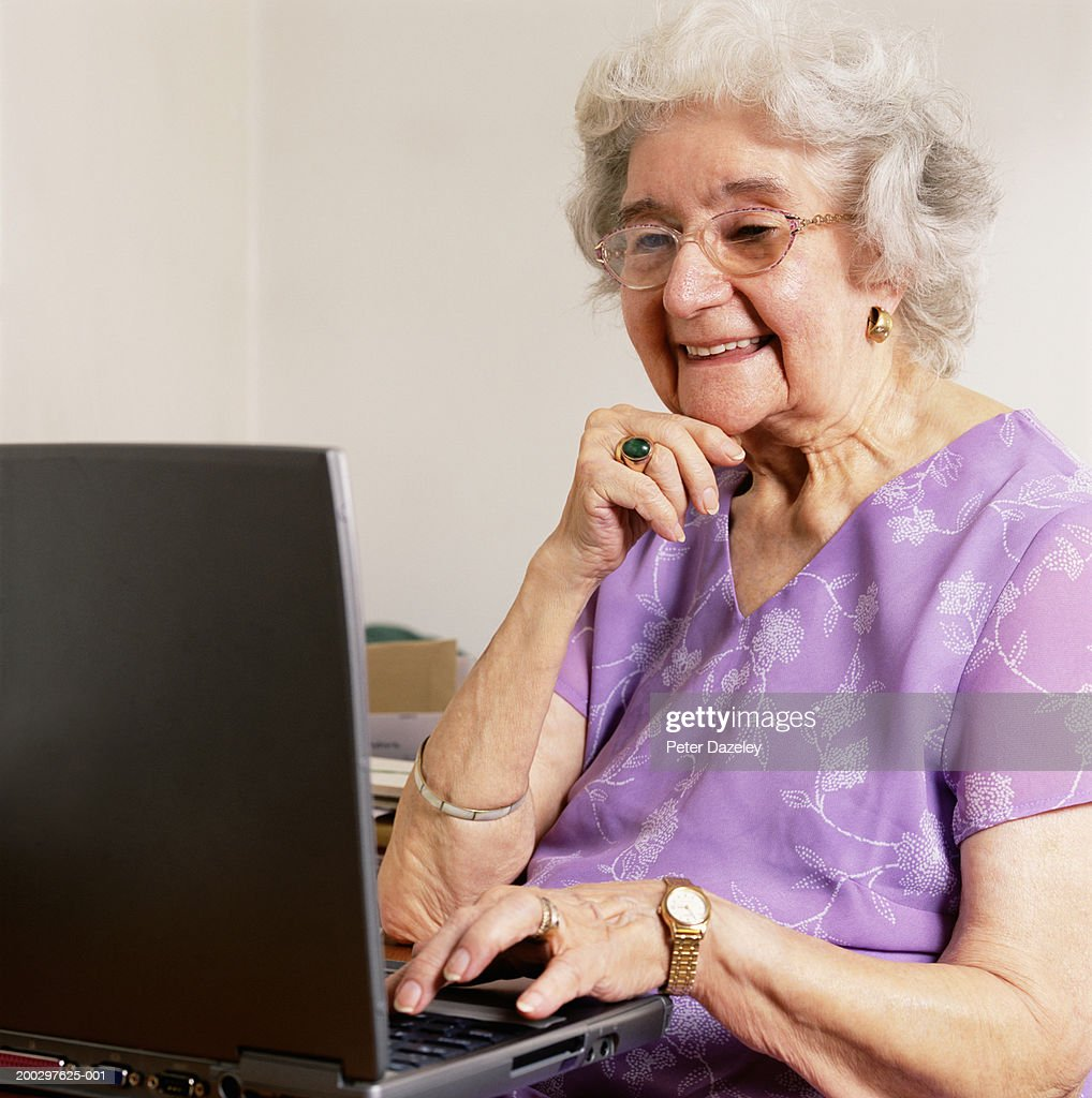 Senior woman using laptop computer, smiling : Stock Photo