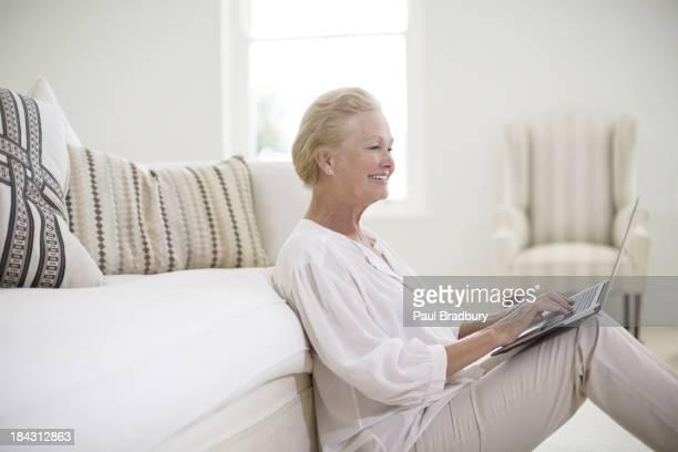 Senior woman using laptop on living room floor