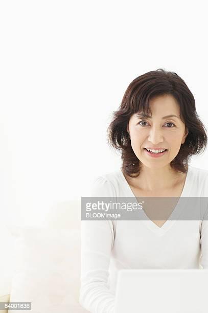 Senior woman using laptop PC, studio shot