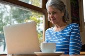 Senior woman using laptop in café