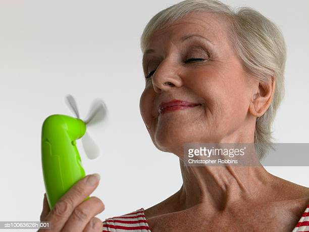 Senior woman using miniature ventilator, smiling with eyes shut, close-up