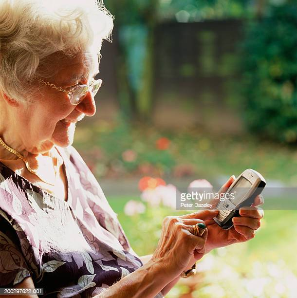 Senior woman using mobile phone, smiling, side view