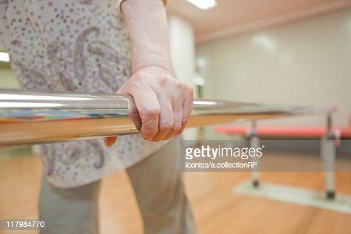 Senior woman using parallel bars, Kanagawa Prefecture, Honshu, Japan