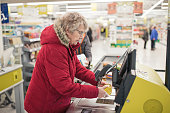 Senior woman using a self service checkout machine at a supermarket.