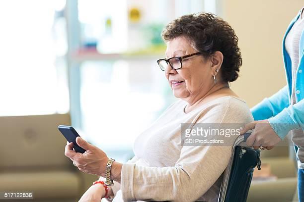 Senior woman using smart phone in nursing home