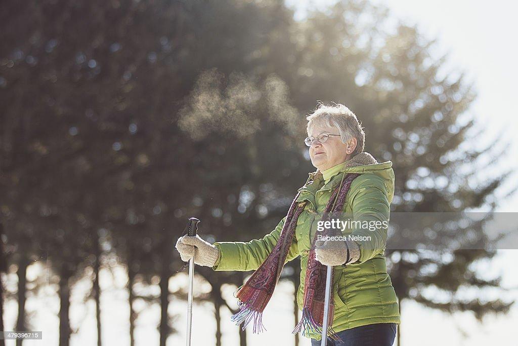 Senior woman using snow shoes
