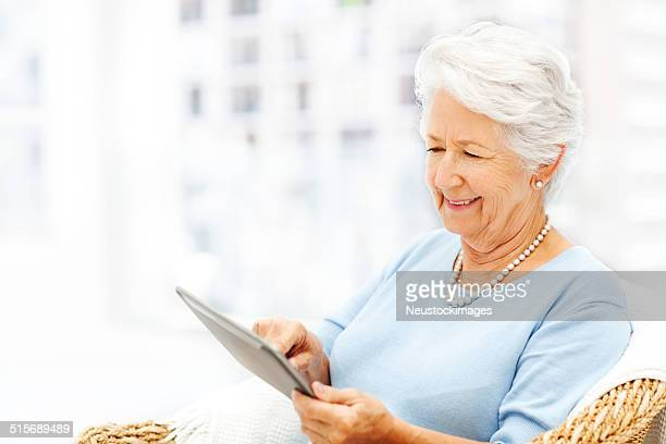 Senior Woman Using Tablet Computer On Wicker Chair