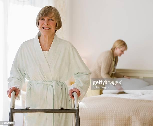 Senior woman using walker in bedroom