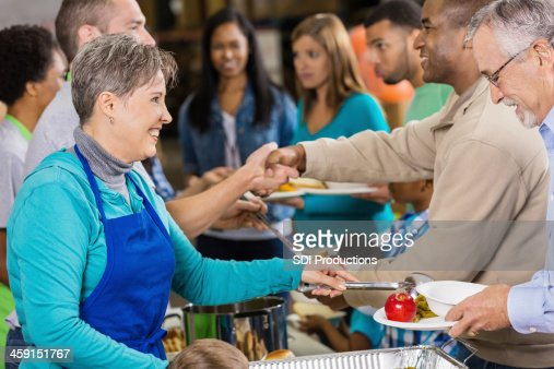 Senior woman volunteering and serving hot meal to people