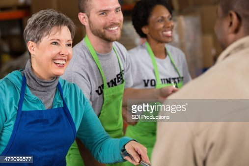 Senior woman volunteering at food bank soup kitchen