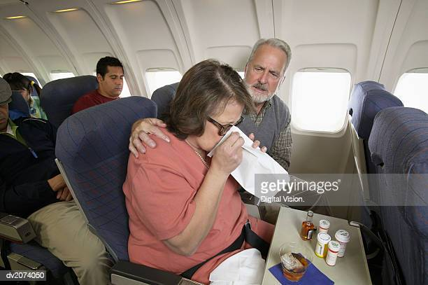 Senior Woman Vomiting Into a Sick Bag During a Flight on a Plane