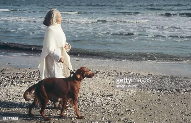 Senior woman walking dog by the sea