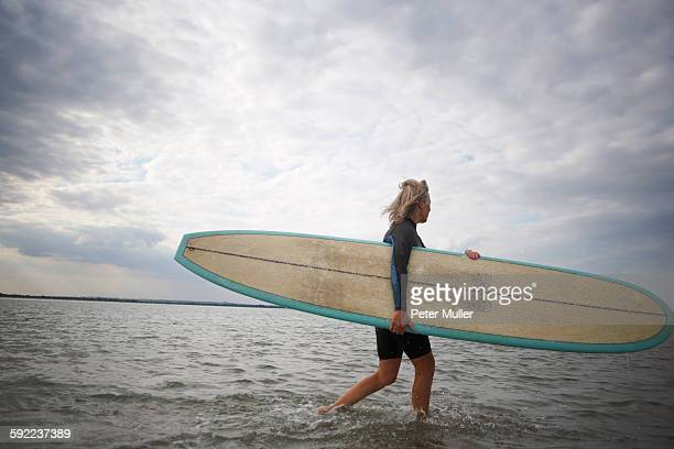 Senior woman walking from sea, carrying surfboard