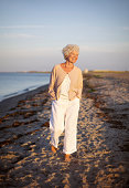 Image of senior woman walking on the beach. Happy and relaxed caucasian female strolling on the beach.