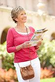 Senior Woman Walking Through City Street With Map