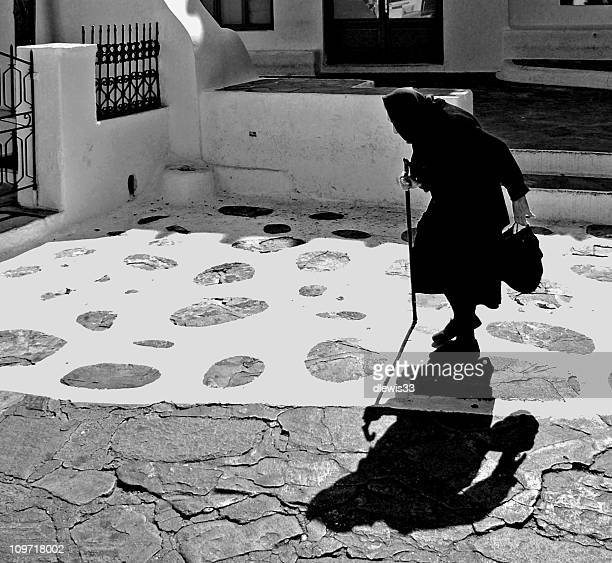 Senior Woman Walking With Cane in Town, Black and White