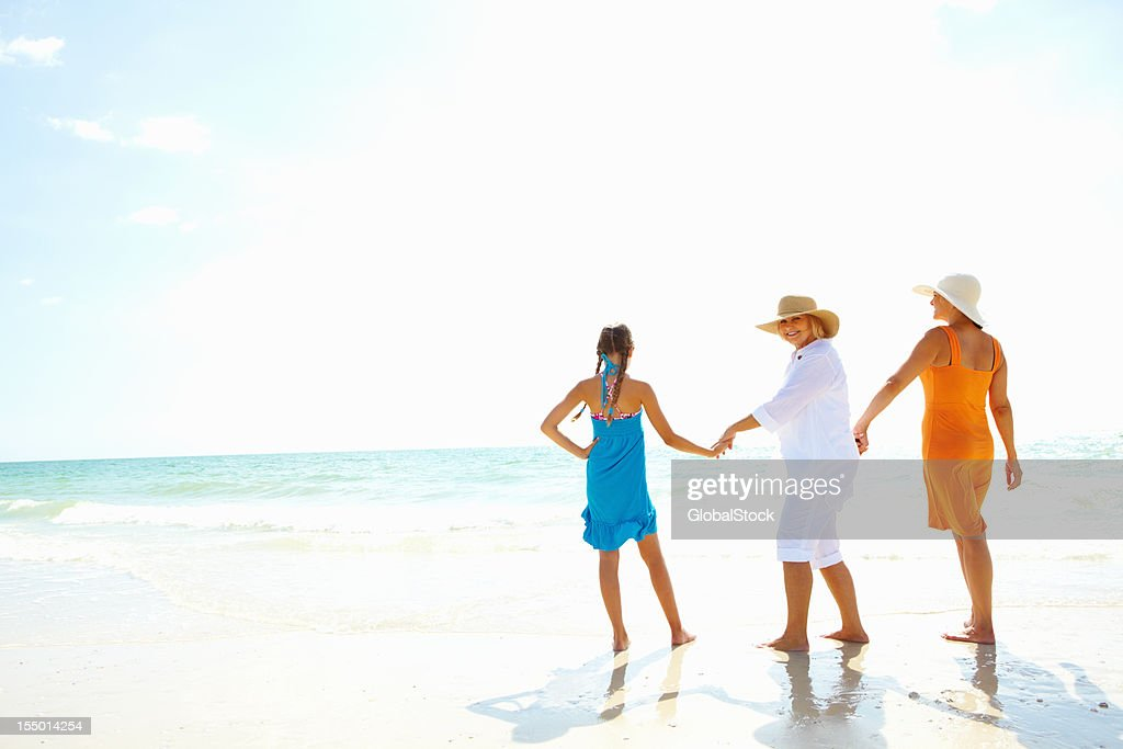 Senior woman walking with daughter and granddaughter on the beach : Stock Photo