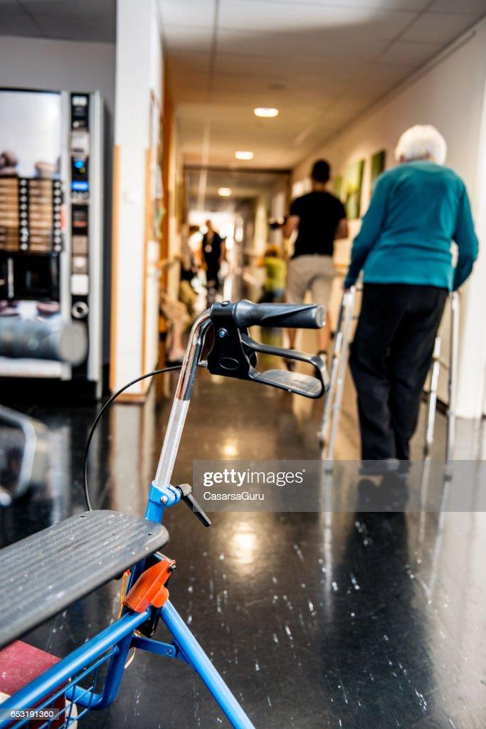 Senior Woman Walking mit Mobilität Walker In den Ruhestand-Center : Stock-Foto