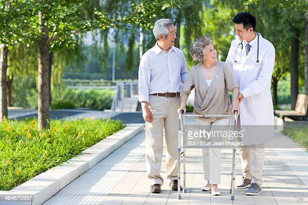 Senior woman walking with walking frame under doctor and  husband's assistance