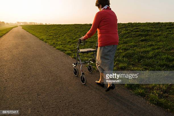Senior woman walking with wheeled walker on a path