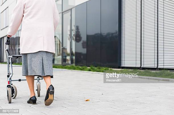 Senior woman walking with wheeled walker on pavement